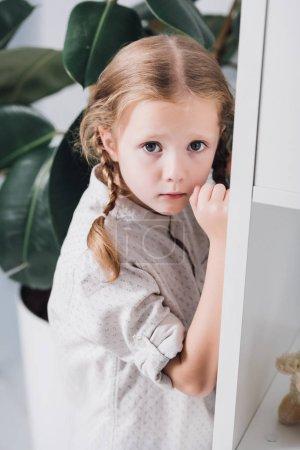 Photo pour Effrayé petit enfant debout derrière les étagères et regardant la caméra - image libre de droit