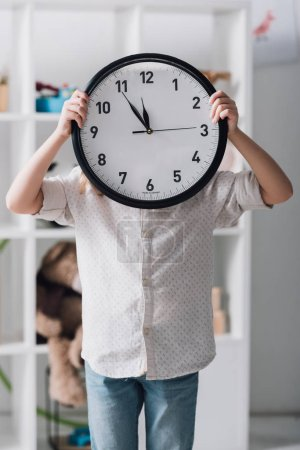 little child covering face with big clock