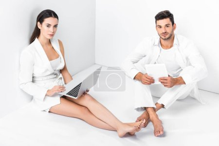 adult couple in total white sitting on floor and using digital devices