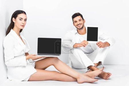 adult couple sitting in white room with laptop and digital tablet
