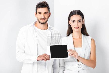 sonriente pareja adulto en blanco total, mostrando la pantalla en blanco en la pantalla de la tableta digital