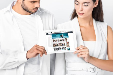 close up of adult couple showing amazon app on digital tablet screen isolated on white