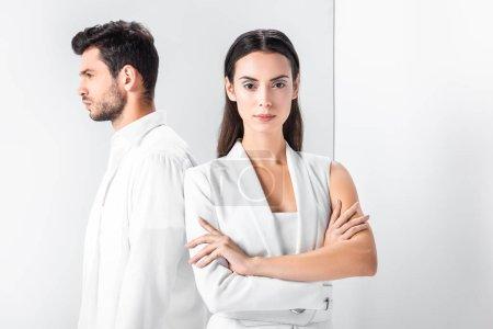 Foto de Mujer elegante en total blanco de pie con los brazos cruzados cerca hombre - Imagen libre de derechos