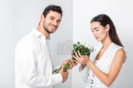 close up of adult woman gently holding bouquet while happy man smiling