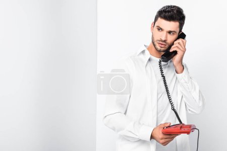 close up of handsome man talking on retro red telephone