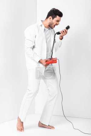 angry barefoot man in total white screaming in retro telephone handset