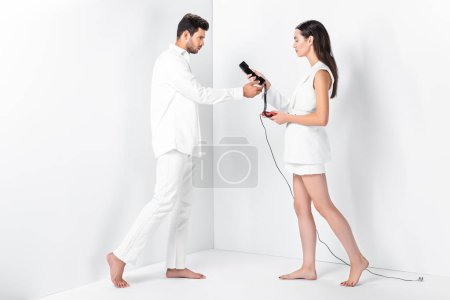 adult couple in total white with vintage telephone handset