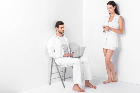 Foto de Hombre adulto en blanco total con portátil y elegante mujer escribiendo en smartphone - Imagen libre de derechos