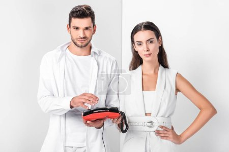 adult couple in total white holding vintage red telephone handset