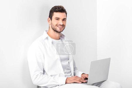 Foto de Adulto sonriendo a guapo en blanco total con laptop - Imagen libre de derechos
