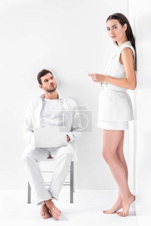 Photo pour Homme adulte en blanc total assis sur la chaise et tapant sur ordinateur portable tout en attrayant femme en utilisant smartphone - image libre de droit