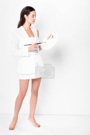 adult beautiful woman in total white posing with palette and paintbrush