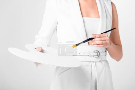female artist in total white posing with palette and paintbrush isolated on white