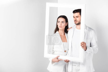 Photo for Adult couple holding white frame together - Royalty Free Image