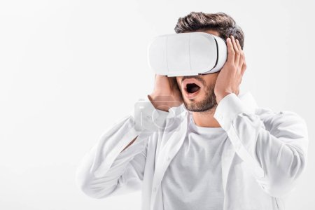 close up of scared adult man in total white wearing virtual reality headset isolated on white