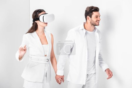 adult man walking with woman in virtual reality headset