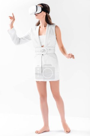 barefoot woman in total white gesturing in virtual reality glasses isolated on white
