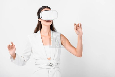 Photo for Close up of adult woman gesturing in virtual reality headset isolated on white - Royalty Free Image