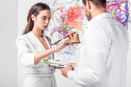 close up of adult couple in total white drawing together with paintbrushes on clothes