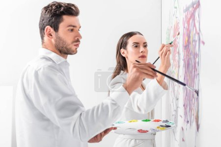 close up of adult couple in total white drawing together on wall