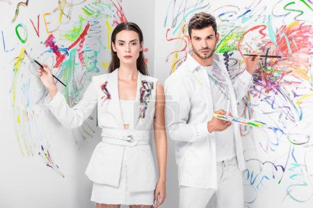 fashion shoot of couple in total white drawing with paints on wall