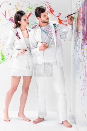 barefoot couple in total white drawing with paints on wall