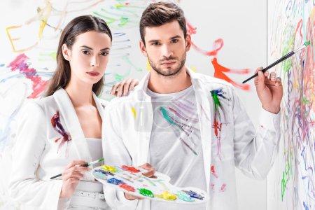 Photo pour Shooting de mode de couple en total blanc dessin avec peintures sur mur - image libre de droit