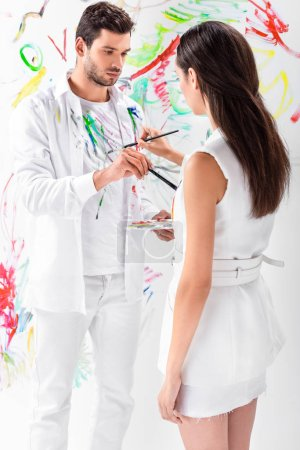 close up of adult couple drawing on clothes against painted wall