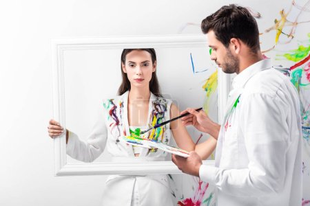 adult woman standing with white frame while man holding drawing equipment
