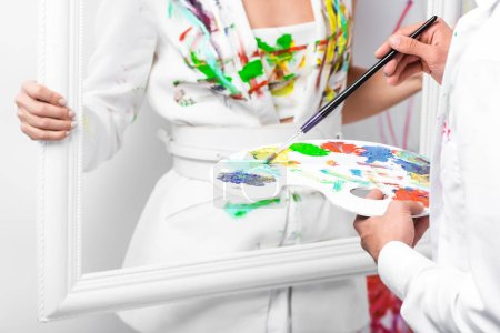 close up of adult man drawing on white clothes with paintbrush while woman holding frame