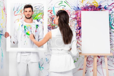 beautiful adult woman drawing on clothes while man holding frame near painted wall