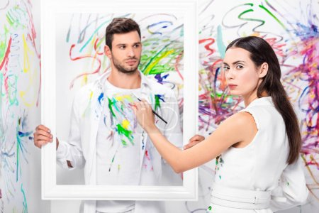 close up of adult man holding white frame while woman painting clothes