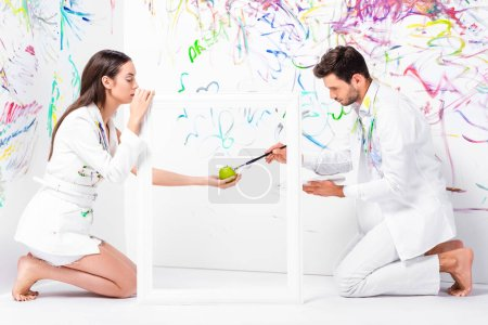 barefoot couple painting apple in frame with paintbrush