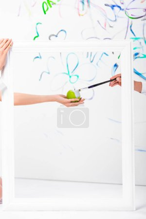 close up of couple painting apple in frame with paintbrush