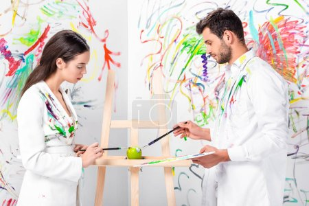 adult couple painting green apple on easel