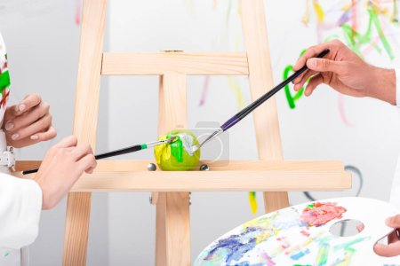 close up of adult couple painting green apple on easel with paintbrushes