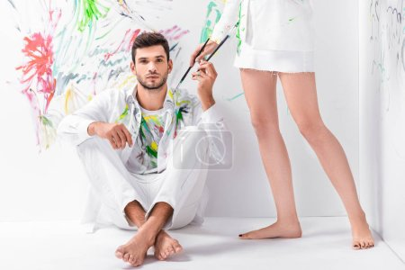close up of couple in painted white clothes with drawing equipment