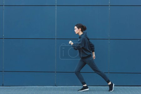 Photo for Active adult sportswoman jogging in sportswear near building - Royalty Free Image