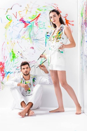 barefoot couple in painted white clothes with drawing equipment