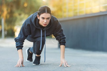 active adult sportswoman exercising before jogging on street