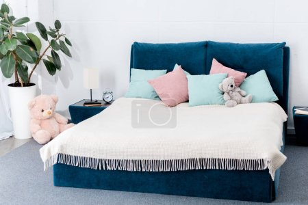 interior of bedroom with pink and blue pillows and teddy bears