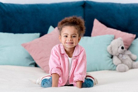 Photo for Smiling african american kid sitting on the bed - Royalty Free Image