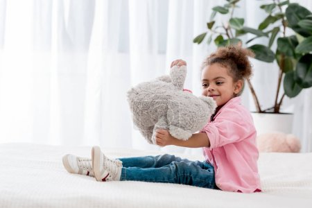 Cute african american child sitting on the bed and playing with her teddy bear