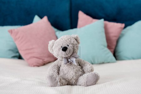 teddy bear sitting on the bed with pillows on background