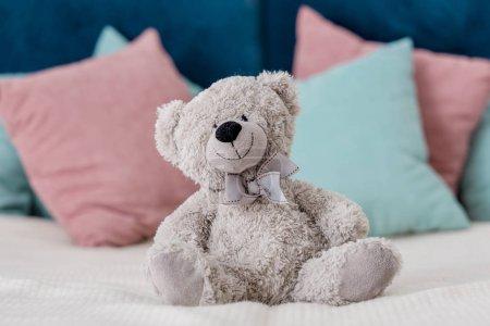 Photo pour Gros plan vue horizontale de l'ours en peluche assis sur le lit avec des oreillers sur le fond - image libre de droit