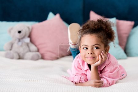 Dreamy African american kid lying on the bed