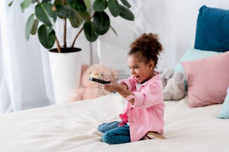 Emotional  African american child sitting on the bed with tv remote and switching the channels
