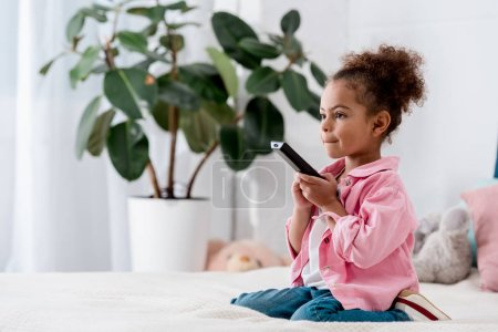 Curly African american kid sitting on the bed and watching tv with remote in her hands
