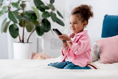Excited  African american kid sitting on the bed with tv remote