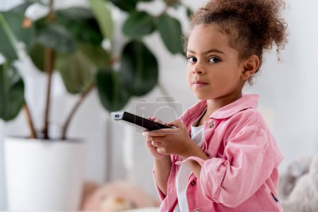 close up of African american child sitting with tv remote